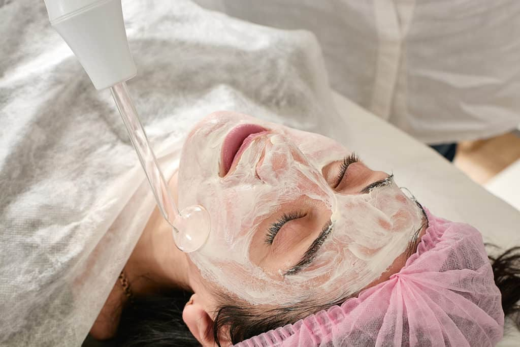 An image of a young woman in beauty salon doing laser rejuvenation and toning on her face.