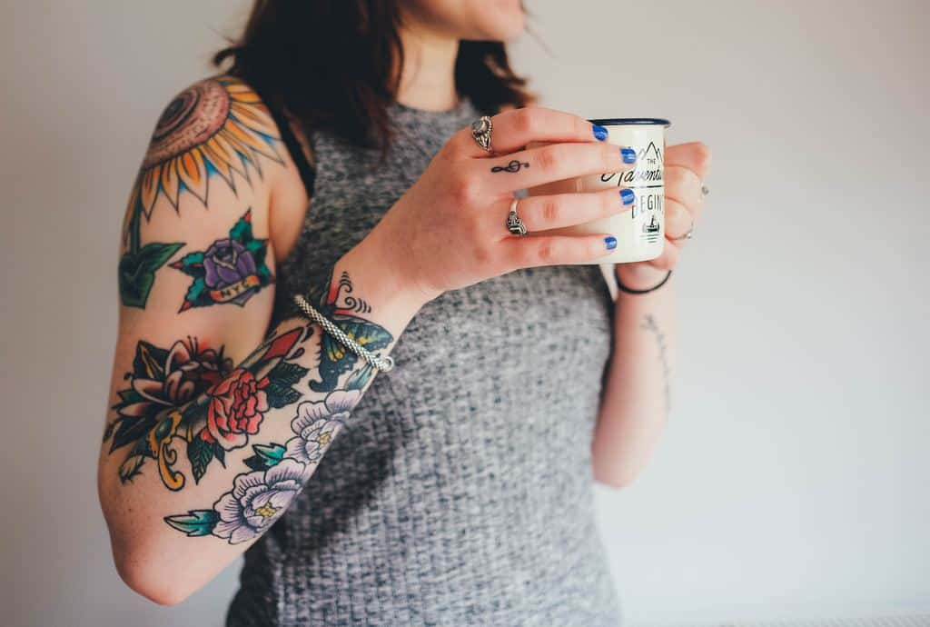 An image of a young women with a tattoo sleeve holding a cup of coffee